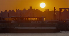 Sun setting over East River Ferry boats docked in marina Stock Footage