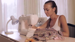 Young woman sews on the sewing machine Stock Footage
