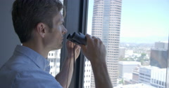 Man looks through binoculars from high office windows at the city of Downtown Lo Stock Footage