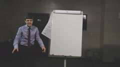 Expressive businessman giving a presentation with flipchart Stock Footage