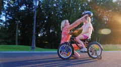 Mother wears a crash helmet daughter, who sits on a children's bicycle. Concept Stock Footage