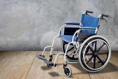 Wheelchair on wooden floor Stock Photos