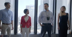 Business team stands by windows in Downtown LA office 4K Stock Footage