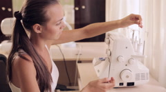Seamstresses is threading needle on sewing machine Stock Footage