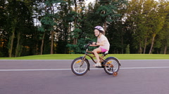 Girl five years in a helmet riding a bike. In the well-kept park on a background Stock Footage