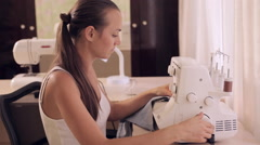 Beautiful woman sews. Powered by overlock. Stock Footage