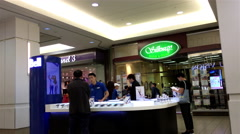 People asking sales clerk about cellphone plan at bell booth Stock Footage