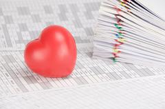 Red heart have blur pile overload paperwork as background Stock Photos