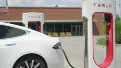 CLOSE UP: White electric car recharging batteries fast at Tesla Supercharger Stock Footage