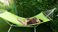 Garden. A young dark-haired woman resting in a hammock. Afternoon sleep. 4K Stock Footage
