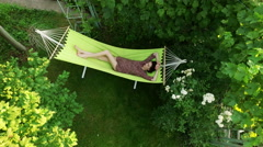 A young dark-haired woman resting in a hammock. Afternoon sleep. Top view. 4K Stock Footage