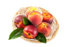 Fruits of peach and nectarine in a wicker dish. Stock Photos