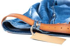 Blue jeans with a leather strap and tag. Stock Photos