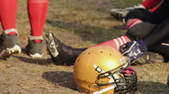 American football player sitting on the pitch, having rest after hard training Stock Footage