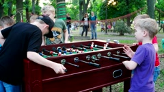 Children in the park playing table football Stock Footage