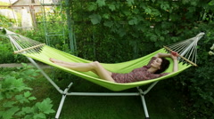 Garden. A young dark-haired woman resting in a hammock. Close-up shoot. 4K Stock Footage