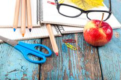 Notepad, pencils, scissors, paper clips and glasses. Stock Photos