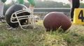 American football players training on a sunny day, closeup of helmet and ball HD Footage