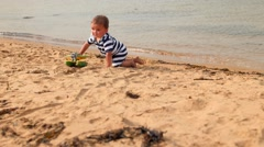 Little boy playing on beautiful ocean beach in the sand Stock Footage