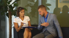 Businesswoman and a businessman in the office to discuss the business plan Arkistovideo