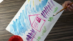 Child hand with brushes drawing on white paper top view Stock Footage