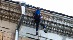 Steepljack worker repair house front in Moscow,  time lapse Stock Footage