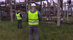 Electrician engineer checking blueprint in substation Stock Footage