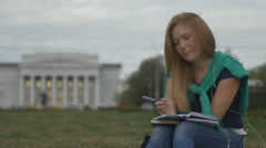 Student makes notes in a notebook Stock Footage