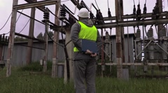 Electrician engineer checking documentation at substation Stock Footage