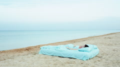 Girl lies on a bed at the sea beach Stock Footage