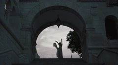 Silhouette of gorgeous bride gracefully dancing under ancient arch in castle at Stock Footage