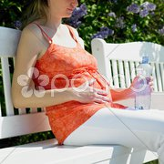 Pregnat woman with bottle of water sitting on bench Stock Photos