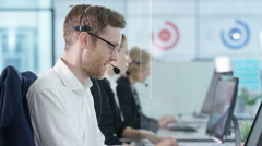 4K Friendly customer service operators taking calls in busy call center Stock Footage
