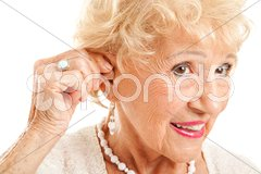 Senior Woman Inserts Hearing Aid Stock Photos