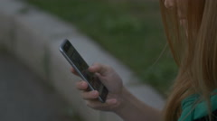 The girl looks at the phone Stock Footage