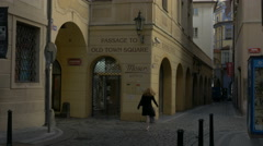 Tilt up narrow Prague street to show the Clock Tower Stock Footage