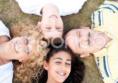 Happy family of four on grass Stock Photos