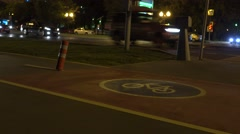 Cyclist and roller passing by on urban bike path at night. 4K shot Stock Footage