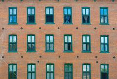 Brick wall and windows facade of urban apartments Stock Photos