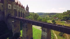 Tourists crossing the bridge to gohtic Corvin Castle on a sunny summer day Stock Footage