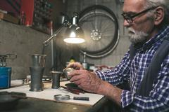 Senior man looking at bottom of antique tin vase. Stock Photos