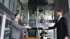 4K Businessmen meet & shake hands in lobby area of large modern office building Stock Footage