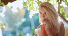 Young, beautiful woman sitting in a restaurant enjoying a cool drink Stock Footage
