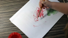 Figure paints on a sheet, baby hands Stock Footage