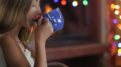 A young girl sips hot drink in front of fireplace and uses her smart phone Stock Footage