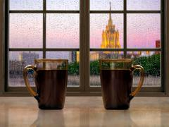Two mugs with a hot drink - tea or coffee on the window sill of the window. D Stock Photos