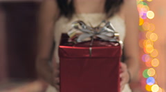 A young woman presents a red wrapped gift with a silver bow towards the camera Stock Footage