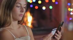 An attractive woman ordering online from her phone with a credit card Stock Footage