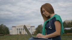 Student sitting at a laptop near the University Stock Footage