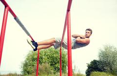 Young man doing sit up on parallel bars outdoors Stock Photos